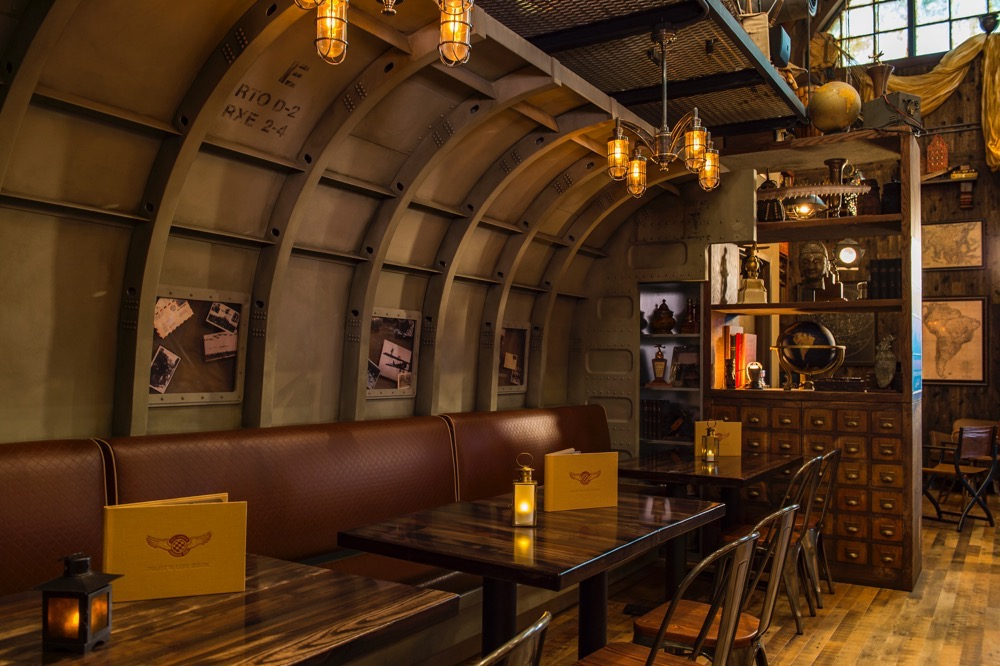 "An aviation-themed lounge, Jock Lindsey's Hangar Bar features unique cocktails and small plates at its prime location along Lake Buena Vista. Ardent fans of the ""Indiana Jones"" films may recognize Jock Lindsey as Indy's frequent pilot. In the main room, guests can discover an expansive bar, aviation decor filling the room, vintage travel posters covering the walls and correspondence between Jock, Indy and their fellow adventurers on display. Jock Lindsey's Hangar Bar is located at The Landing area at Disney Springs in Lake Buena Vista, Fla. (Matt Stroshane, photographer) (c)Disney"